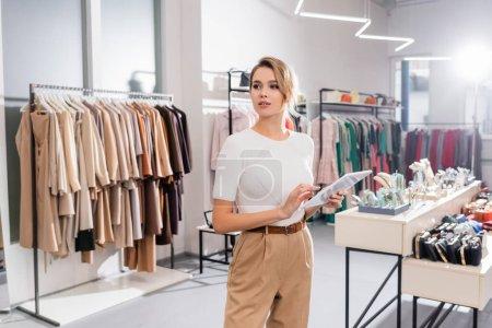 Photo pour Jeune vendeur utilisant une tablette numérique tout en se tenant dans la salle d'exposition avec des vêtements - image libre de droit