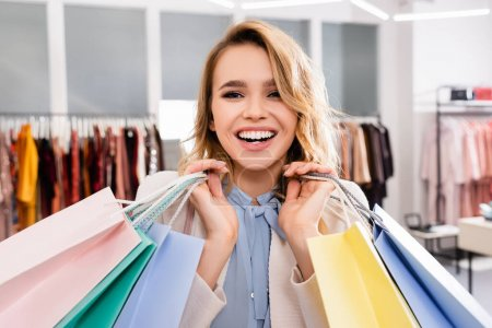 Cheerful woman with shopping bags looking at camera in showroom