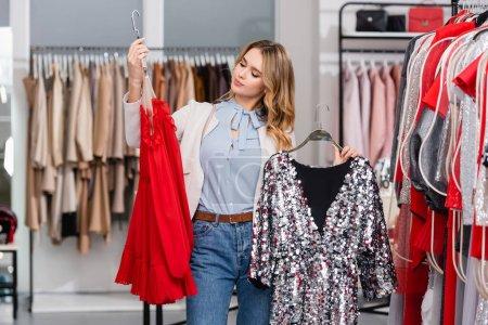 Jeune femme choisissant robe sur cintre près des vêtements dans le showroom