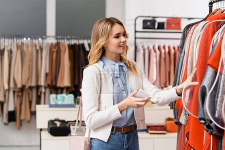 Cheerful customer holding smartphone while choosing clothes in showroom