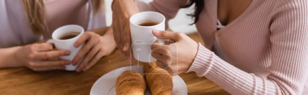 cropped view of lesbian couple holding cups near croissants on table, banner
