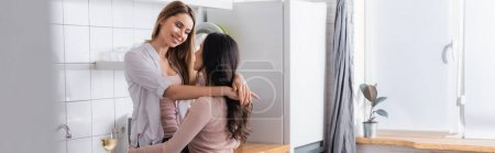 happy woman hugging girlfriend in kitchen, banner
