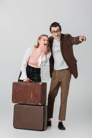 Photo for Excited woman near suitcases and man pointing with finger on grey background - Royalty Free Image