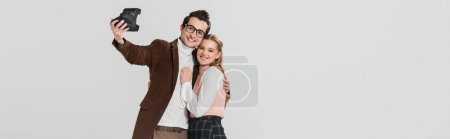 happy couple in retro clothes taking selfie on vintage camera isolated on grey, banner