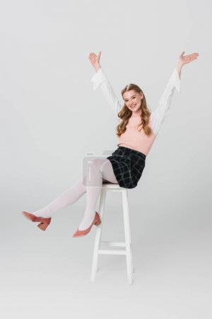 cheerful woman in vintage outfit sitting on high stool with raised hands on grey