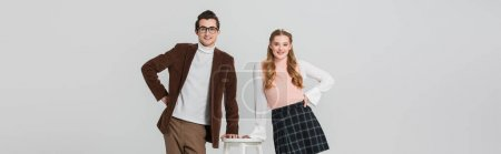 joyful couple in retro clothes posing with hands on hips near high stool isolated on grey, banner