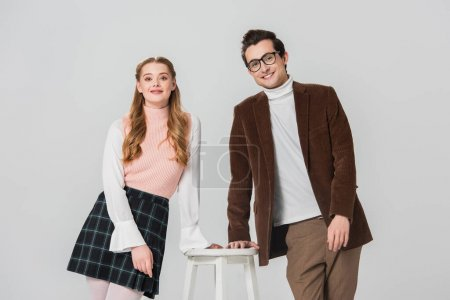 smiling couple in retro clothes smiling at camera near high stool isolated on grey
