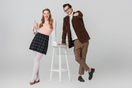 excited and cheerful couple showing thumbs up while standing near high stool on grey background