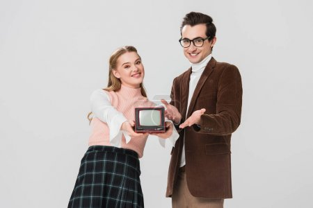 Photo for Man in eyeglasses pointing at vintage tv in hands of cheerful woman isolated on grey - Royalty Free Image