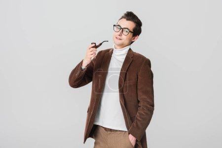 Photo pour Homme élégant dans vieux blazer pipe fumeur tout en posant avec la main dans la poche isolé sur gris - image libre de droit