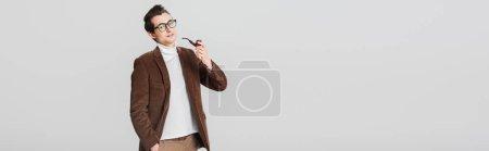Photo pour Vieil homme à la mode regardant la caméra tout en posant avec tuyau fumeur isolé sur gris, bannière - image libre de droit