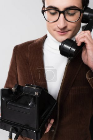 old fashioned man in brown blazer talking on retro telephone isolated on grey