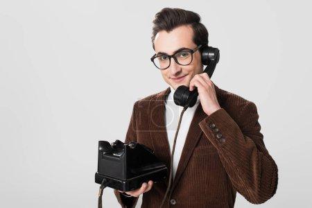 smiling man in eyeglasses and velvet blazer talking on vintage phone isolated on grey