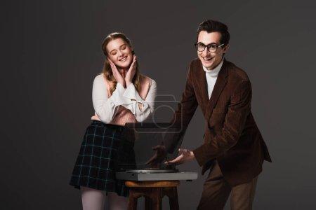 Photo pour Joyeux homme pointant vers tourne-disque près heureux femme isolée sur noir - image libre de droit