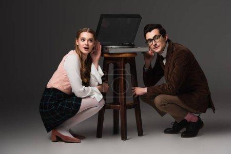 Photo pour Couple excité écouter de la musique près du tourne-disque sur fond gris foncé - image libre de droit