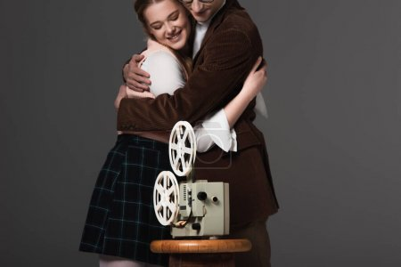 happy couple embracing near vintage film projector isolated on black