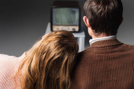 Photo pour Vue arrière de la femme appuyée sur l'épaule de l'homme tout en regardant la télévision vintage sur fond gris - image libre de droit