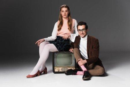 vieille femme assise sur vintage tv près homme souriant sur fond gris