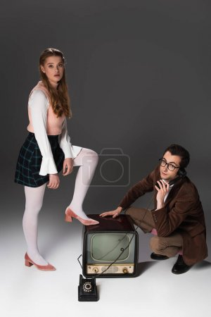 pretty woman stepping on vintage tv near man talking on telephone on grey background
