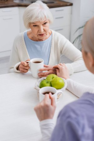senior woman talking to social worker near fresh apples and cups of tea, blurred foreground