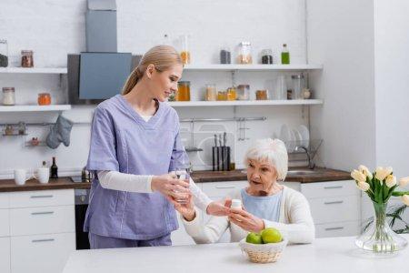 Photo pour Jeune infirmière donnant un verre d'eau et des médicaments à une femme âgée dans la cuisine - image libre de droit