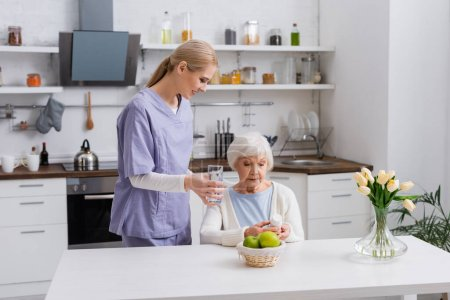 young nurse giving glass of water to elderly woman holding pills container in kitchen