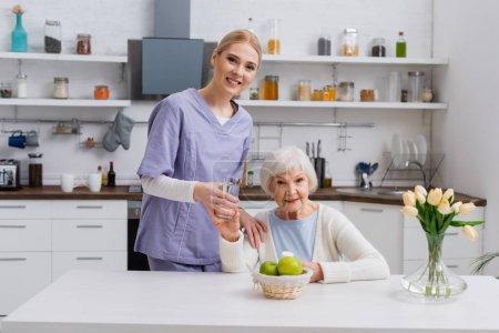 Photo pour Jeune infirmière et femme âgée souriant à la caméra tout en tenant un verre d'eau et de médicaments dans la cuisine - image libre de droit
