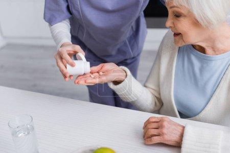 Sozialarbeiterin verteilt Medikamente an ältere Frau