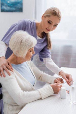 Photo pour Travailleur social touchant l'épaule de la femme âgée pointant vers les pilules près du verre d'eau - image libre de droit