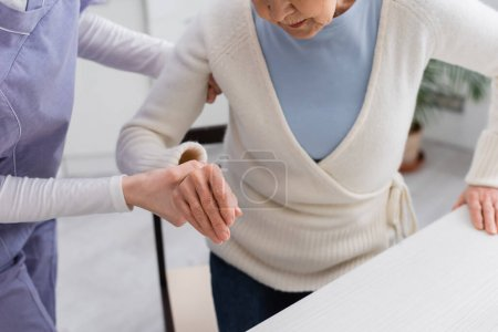 cropped view of social worker helping senior woman getting up