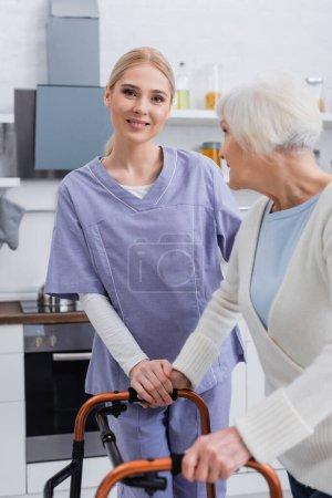 Lächelnde Krankenschwester blickt in die Kamera in der Nähe einer betagten Frau mit Rollator