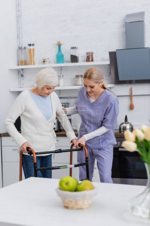 young nurse helping elderly woman walking with medical walkers in kitchen, blurred foreground