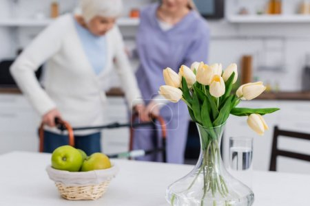 selective focus of tulips and apples near blurred social worker helping senior woman with medical walkers