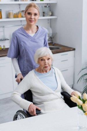 junge Krankenschwester und ältere behinderte Frau schaut in die Kamera in der Küche