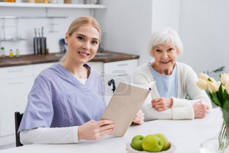 Lächelnde Krankenschwester mit Buch blickt in die Kamera in der Nähe einer glücklichen älteren Frau in der Küche