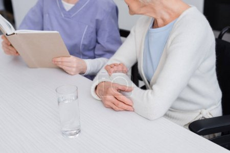 partial view of nurse reading book to aged woman near glass of water, blurred background
