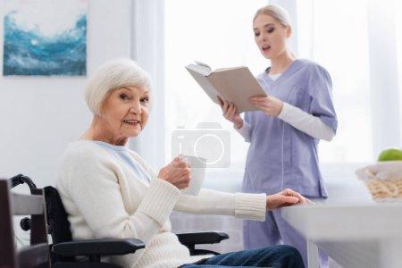 anciana discapacitada con taza de té mirando la cámara cerca de la enfermera leyendo libro sobre fondo borroso