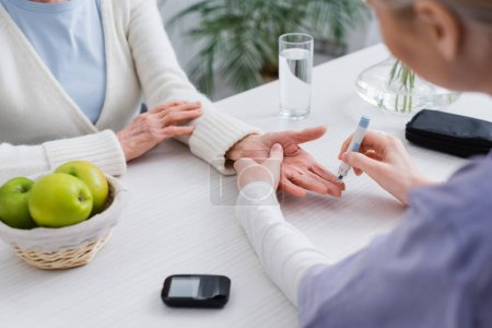 partial view of nurse doing insulin injection to elderly diabetic woman near glucometer, blurred foreground
