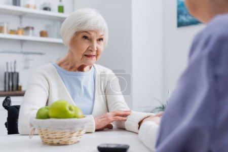mujer diabética mayor mirando a la trabajadora social cerca del glucosímetro borroso