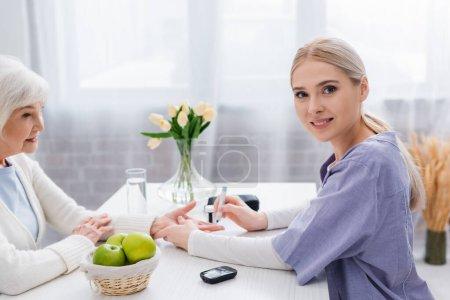 Photo pour Infirmière souriante regardant la caméra pendant l'injection d'insuline à une femme diabétique âgée - image libre de droit