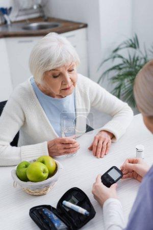 Photo pour Vue grand angle de la femme âgée avec verre d'eau près travailleur social avec glucomètre - image libre de droit