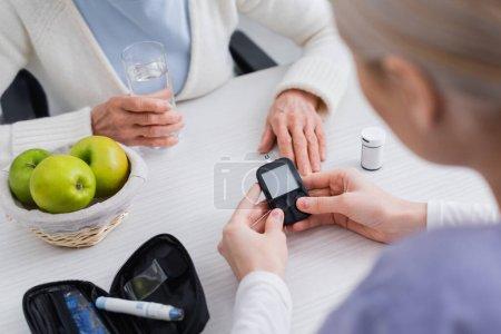 vue recadrée du travailleur social avec glucomètre près d'une femme diabétique âgée avec verre d'eau, avant-plan flou
