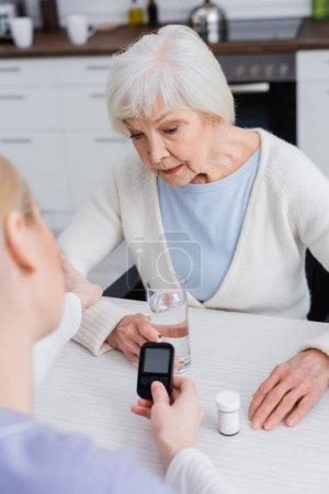 Enfermera sosteniendo glucosímetro cerca de la mujer diabética mayor y envase de píldoras, borrosa primer plano