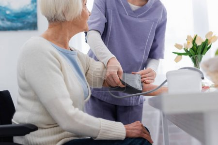cropped view of nurse measuring blood pressure of elderly woman at home