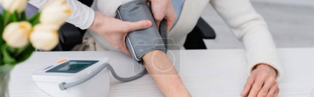 cropped view of social worker putting cuff of tonometer on hand of senior woman, banner