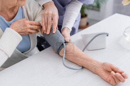 cropped view of social worker measuring blood pressure of senior woman with tonometer