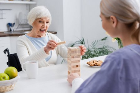 excited senior woman playing wooden tower game with social worker on blurred foreground