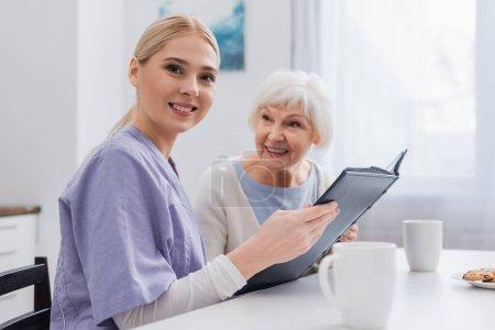 Glückliche Sozialarbeiterin blickt in die Kamera, während sie ein Fotoalbum in der Nähe einer betagten Frau hält