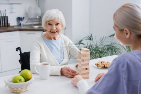 aged disabled woman smiling at camera while playing wood blocks game with nurse