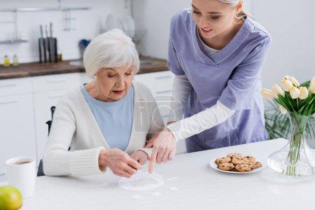 junge Krankenschwester zeigt auf Puzzle in der Nähe einer älteren Frau in Küche